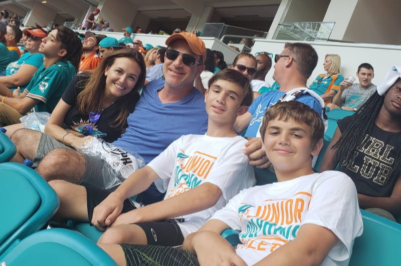 the family together at a football game, positive parenting tips