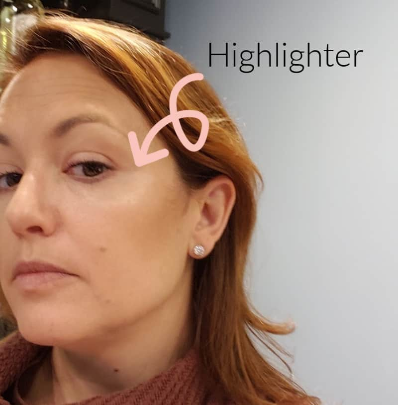 applying highlighter to the upper cheekbones