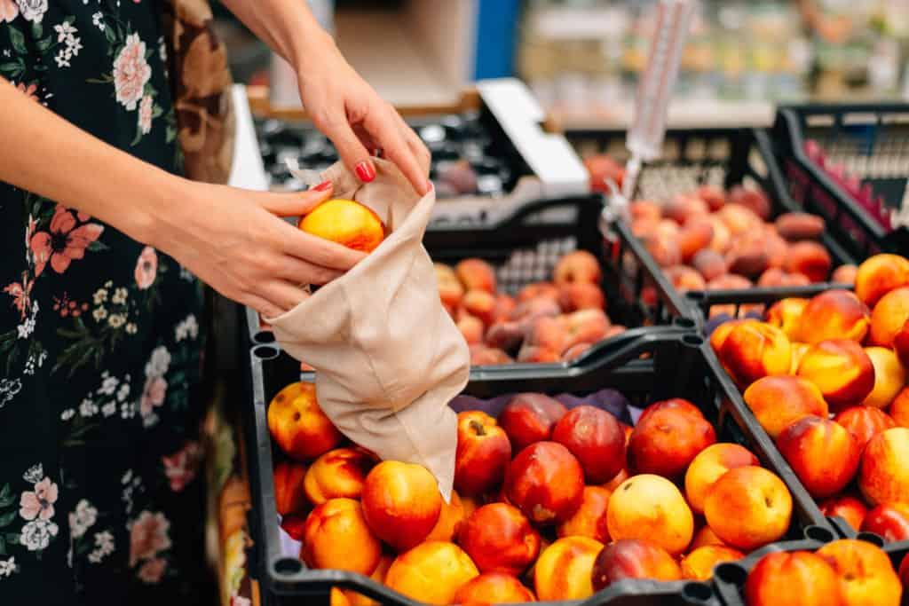 conscious consumption woman using a reusable produce bag